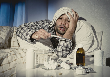Foto de sick wasted man lying in bed wearing pajama suffering cold and winter flu virus having medicine tablets in health care concept looking temperature on thermometer - Imagen libre de derechos