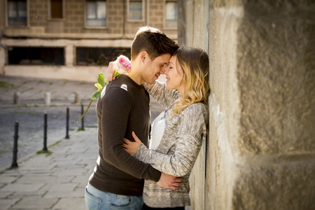candid portrait of beautiful European couple with rose in love kissing on street alley celebrating Valentines day with passion against stone wall on urban background