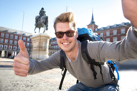 Foto de young attractive student backpacker tourist taking selfie photo with mobile phone outdoors enjoying holidays travel destination in tourism and exploring concept - Imagen libre de derechos