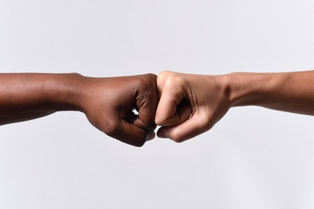Photo for black African American race female hand touching knuckles with white Caucasian woman in agreement partnership and cooperation multiracial diversity immigration concept - Royalty Free Image