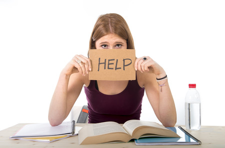 Foto de young beautiful college student girl studying for university exam in stress asking for help under test pressure sitting on desk with book in youth education concept - Imagen libre de derechos