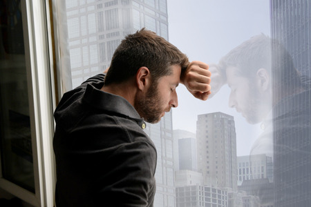 Foto de young attractive man leaning desperate on window glass at business district home, looking worried, depressed, thoughtful and lonely suffering depression in work or personal problems - Imagen libre de derechos