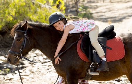 Photo pour sweet beautiful young girl 7 or 8 years old riding pony horse hugging and smiling happy wearing safety jockey helmet posing outdoors on countryside in summer holiday - image libre de droit