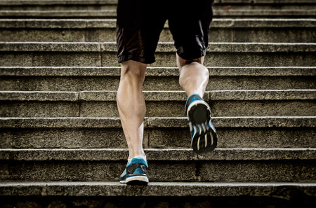 Foto de athletic legs of young sport man with sharp scarf muscles running on staircase steps jogging in urban training workout or runner competition in fitness and healthy lifestyle concept - Imagen libre de derechos