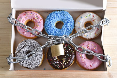 Photo pour box full of tempting delicious donuts wrapped in metal chain and lock in sugar and sweet addiction and diet body and dental care concept - image libre de droit