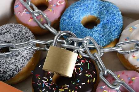 Photo for box full of tempting delicious donuts wrapped in metal chain and lock in sugar and sweet addiction and diet body and dental care concept - Royalty Free Image