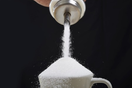 Photo for man hand with sugar bowl pouring a crazy lot of it spilling out everywhere in full coffee cup in insane sugar addiction and unhealthy nutrition concept isolated on black background - Royalty Free Image