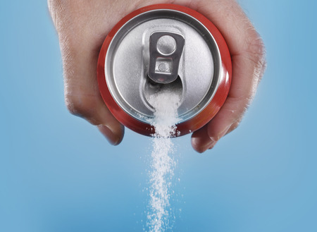 Foto de hand holding soda can pouring a crazy amount of sugar in metaphor of sugar content of a refresh drink isolated on blue background in healthy nutrition, diet and sweet addiction concept - Imagen libre de derechos