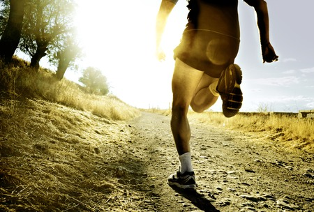 Photo pour close up silhouette legs and feet of extreme cross country man running and training on rural track jogging at sunset with harsh sunlight and lens flare in countryside sport and healthy lifestyle concept - image libre de droit