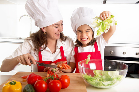 Foto de young mother preparing salad for lunch wearing apron and cook hat at home kitchen with little daughter playing with lettuce and having fun together in healthy nutrition education concept - Imagen libre de derechos