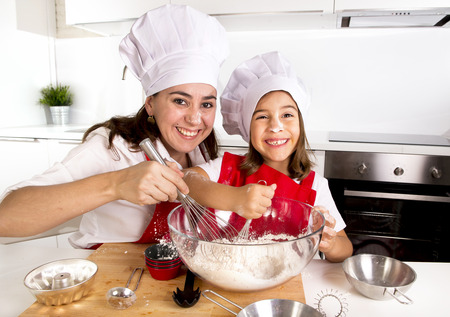 Photo for happy mother baking with little daughter in apron and cook hat working with flour , bowl and spoon preparing dough teaching the kid baking and having fun together - Royalty Free Image