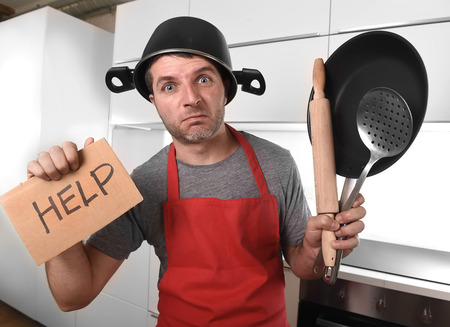Foto per funny 30s Caucasian man holding pan and household with pot on his head in red apron at home kitchen asking for help unable to cook showing panic on cooking with funny face expression - Immagine Royalty Free
