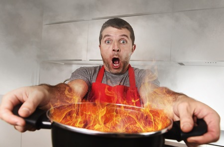 Photo pour young inexperienced home cook with apron holding pot burning in flames with stress and panic face expression in fire in the kitchen and cooking wrong concept - image libre de droit
