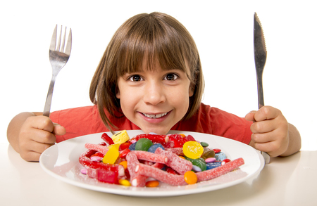 Photo for cute European female child smiling happy eating candy with spoon fork and knife in sugar abuse , unhealthy sweet nutrition concept , children candy addiction and kids  dental care - Royalty Free Image