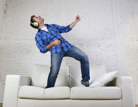 Photo for young attractive 20s or 30s man having fun jumped on home couch listening to music on mobile phone with headphones dancing , singing and playing air guitar happy and crazy - Royalty Free Image