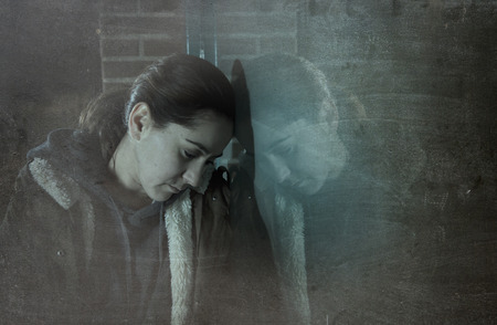 Foto de sad woman alone leaning on street window at night looking desperate suffering depression crying in pain lonely and lost as violence and abuse female victim or addict concept grunge dirty edit - Imagen libre de derechos