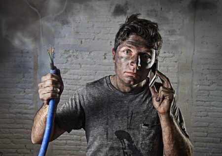 Foto de young man holding electrical cable smoking after electrical accident with dirty burnt face in funny desperate expression calling with mobile phone asking for help in electricity DIY repairs danger concept - Imagen libre de derechos
