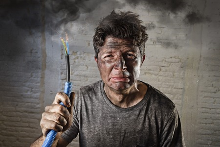 Photo pour young man holding electrical cable smoking after domestic accident with dirty burnt face in funny sad expression in electricity DIY repairs danger concept  in black smoke background - image libre de droit