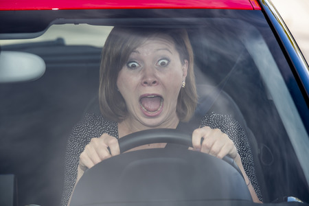 Foto de female rookie new driver young beautiful woman scared and stressed while driving car in fear and shock face expression screaming in panic - Imagen libre de derechos