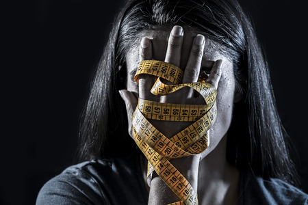 Foto de Close up hands wrapped in tailor measure tape covering face of young depressed and worried girl - Imagen libre de derechos