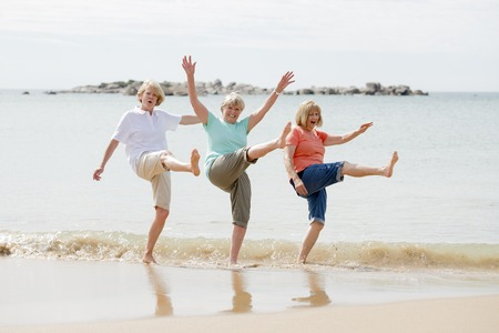 Foto de lovely group of three senior mature retired women on their 60s having fun enjoying together happy walking on the beach smiling playful in female friendship and girlfriends on holidays concept - Imagen libre de derechos