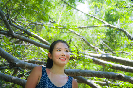 Foto de young pretty and happy Asian Chinese woman taking a walk excursion trip on tropical mountain enjoying nature smiling cheerful in holiday vacation travel and tourism concept - Imagen libre de derechos