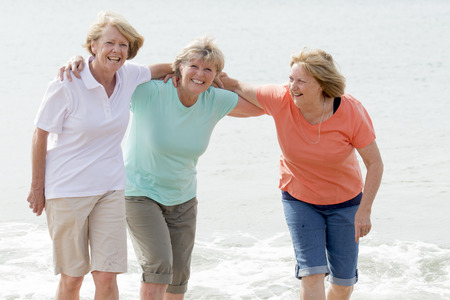 Photo for lovely group of three senior mature retired women on their 60s having fun enjoying together happy walking on the beach smiling playful in female friendship and girlfriends on holidays concept - Royalty Free Image