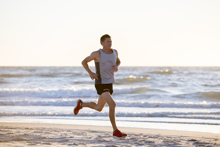 Photo for portrait of young athletic fit and strong runner man training on Summer sunset beach in sea shore running and fitness workout in sport and healthy lifestyle concept - Royalty Free Image