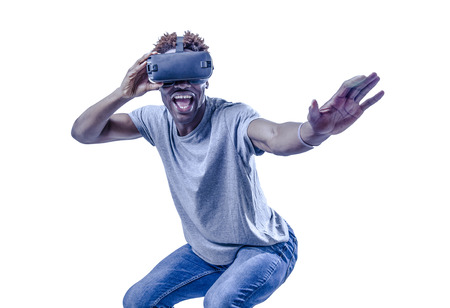 Foto de young active excited afro American man enjoying happy playing with 3d goggles virtual reality video device in gaming and entertainment new technology concept isolated background - Imagen libre de derechos