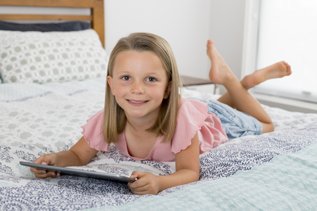 Photo for sweet and beautiful blond 6 or 7 years old young girl lying on bed smiling happy using the internet on digital tablet pad watching and having fun in child relationship with technology concept - Royalty Free Image