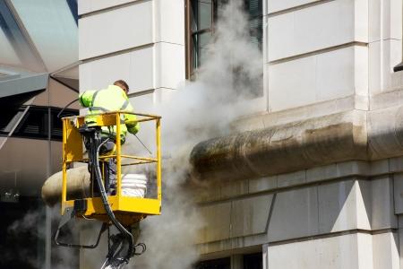 Photo pour a worker washes the facade of the building - image libre de droit