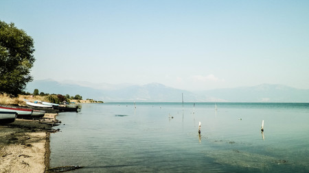 Photo pour Fishing boats on coast of Lake Prespa and Mountains of Galicica National Park. Prespa lake is situated between Macedonia, Greece and Albania, known of it's wild nature and pelican reserve. - image libre de droit