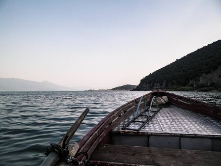 Photo pour Sailing over Lake Prespa in Galicica National Park. Prespa is situated between Macedonia, Greece and Albania, known of it's wild nature and pelican reserve. View from boat. - image libre de droit