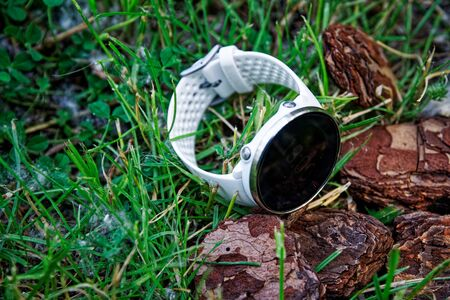 Foto de Sport watch for running white color on the ground in the grass. Fitness watch for tracking daily activity and strength training - Imagen libre de derechos