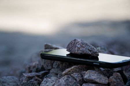 Foto de Cell phone with broken glass on gravel granite stones, unbreakable gadget. - Imagen libre de derechos