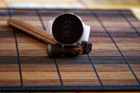 Foto de Sport watch in white color on wooden table, Smart watch for running and fitness training. Hammer with wooden handle on background. - Imagen libre de derechos