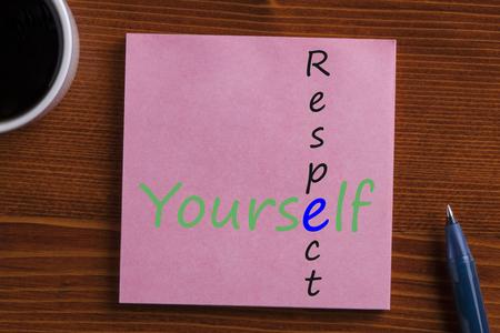Foto de  Respect Yourself in note with pen and cup of coffee on wooden desk. Top view. - Imagen libre de derechos