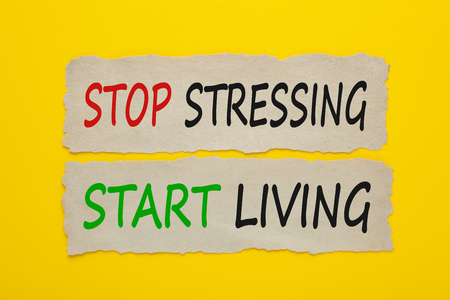 Photo for STOP STRESSING START LIVING written on old torn paper on yellow background. - Royalty Free Image