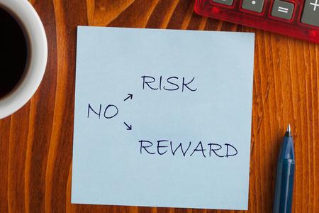 Foto de No Risk No Reward on note with pen a side, cup of coffee and calculator. Business concept - Imagen libre de derechos