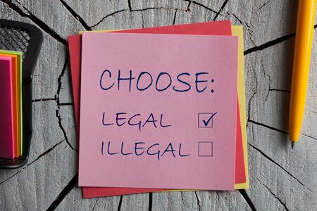Photo pour Choose Legal and illegal on note with pen on wooden surface. - image libre de droit
