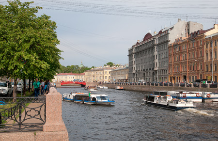 Foto de SAINT-PETERSBURG, RUSSIA - JUNE 11, 2018: People in excursion boats on Moyka River near The Red Bridge in the center of the city - Imagen libre de derechos