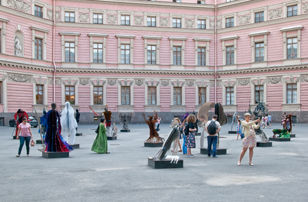 Foto de SAINT-PETERSBURG, RUSSIA - JULY 23, 2018: People looking at the group of modern sculptures In Dante Veritas by Vasily Klyukin in the yard of Mikhailovsky Castle - Imagen libre de derechos