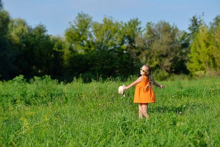 Foto de Happy young girl jumping playing on a meadow in sunny day Children run through the grassy field without a care in the world. - Imagen libre de derechos
