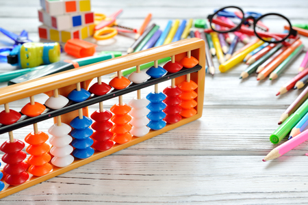 Foto de Close up view of abacus scores mental arithmetic with colorful back to school supplies over white table. Space for text. Flat lay style - Imagen libre de derechos