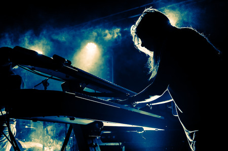 Photo for Female keyboards player on stage during concert, backlight, colors intentionally altered - Royalty Free Image