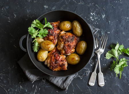 Photo pour One pot baked harissa chicken and new potatoes on a dark background, top view - image libre de droit