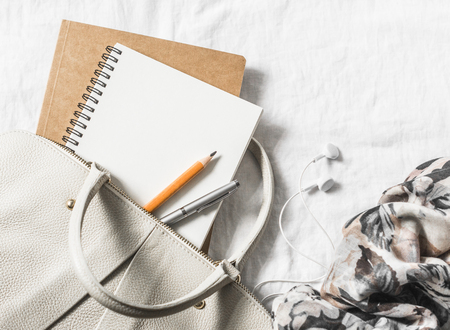 Photo for Womens leather handbag, clean blank notepad, pen and scarf on a light background, top view. Free space for text - Royalty Free Image
