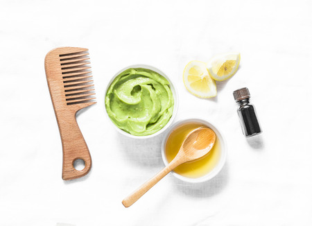 Foto de Avocado, honey hair homemade mask on light background, top view. Natural products for hair health and beauty - Imagen libre de derechos