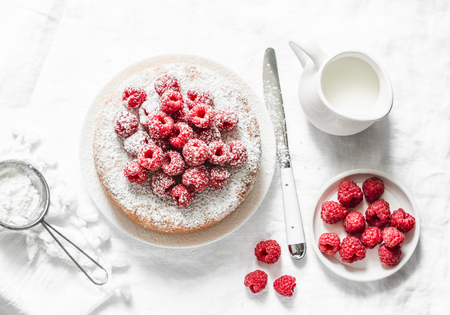 Photo for Simple cake with powdered sugar and fresh raspberries on a light background. Summer berry dessert. Flat lay - Royalty Free Image