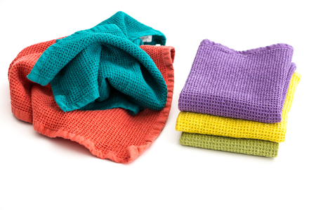 Foto de Pile of  messy and stack of folded colorful kitchen towels, on white background. - Imagen libre de derechos